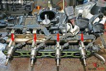 Снятые для чистки топливные форсунки TSI (непосредственный впрыск, показаны стрелками). Компоновка двигателя не позволяет снять форсунки отдельно от топливной рейки и впускного коллектора.